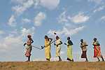 After working together in a community garden, women sing and dance as they walk home on April 12, 2017, atop a dyke they constructed to control flooding around Dong Boma, a Dinka village in South Sudan's Jonglei State. Most of the women's families recently returned home after being displaced by rebel soldiers in December, 2013, and they face serious challenges in rebuilding their village while simultaneously coping with a drought which has devastated their cattle herds.<br /> <br /> The Lutheran World Federation, a member of the ACT Alliance, is helping villagers restart their lives with support for housing, livelihood, and food security.