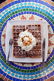 USA, Oregon, Ashland, interior table detail at the colorful Morning Glory Restaurant on Siskiyoui Blvd during breakfast, Gingerbread waffle with whipped cream and pear compote