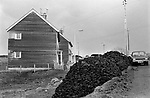 Free peat piled outside local authority council housing Carloway. To be taken by the residents used for hating and hot water.  Isle of Lewis, Outer Hebrides, Scotland 1974.