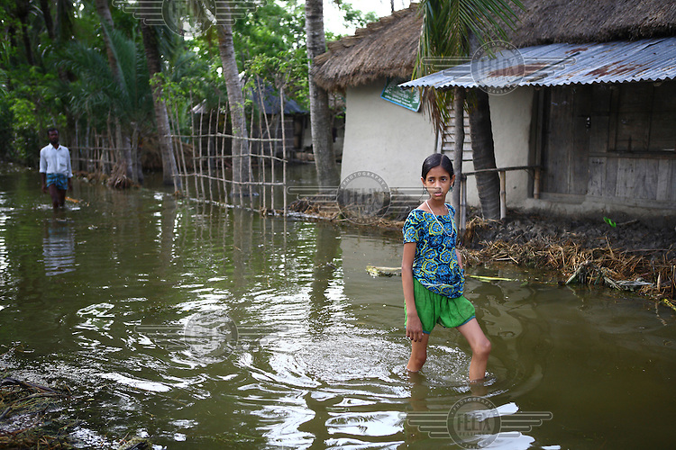 A girl wades through the floodwaters in her village. Thousands of people were displaced in Shyamnagar Upazila, Satkhira district after Cyclone Aila struck Bangladesh on 25/05/2009, triggering tidal surges and floods.