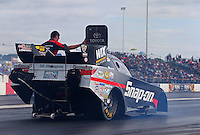 Jun 5, 2015; Englishtown, NJ, USA; A crew member lifts open the roof hatch on the car of NHRA funny car driver Cruz Pedregon to vent the tire smoke out  during qualifying for the Summernationals at Old Bridge Township Raceway Park. Mandatory Credit: Mark J. Rebilas-