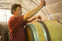 Daniel Le Conte des Floris Domaine Le Conte des Floris, Caux. Pezenas region. Languedoc. Barrel cellar. Drawing a sample with a pipette. Owner winemaker. France. Europe.