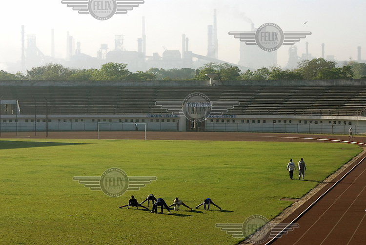 Exercising in the Tata Stadium overlooked by the steel works.  The stadium is one of many sports facilities in the city to be built and managed by Tata Steel, India's largest private steel company.  ..