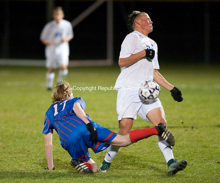FARMINGTON, CT--- -111815JS07--Leis Mills' Frederick Marinelli (20) gets tripped up by Tolland's Brandon Merluzzo (17) during their Class M. semifinal game Wednesday at Tunxis Mead Sports Complex in Farmington. <br /> Jim Shannon Republican-American
