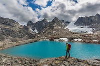 Man pauses while hiking at the edge of a blue lake in the Arrigetch Peaks, Valley of Aquarius, Gates of the Arctic National Park, Alaska