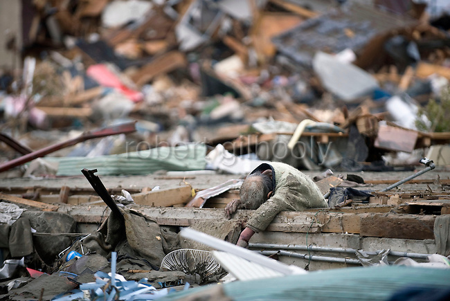 The corpse of a man killed during the March 11 earthquake and tsunami lies in the shattered remains of a community hit my the March 11 tsunami in Ishinomaki, Japan on 15 March, 2011.  Photographer: Robert Gilhooly