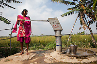 A girl pumps water at a boorwell next to a wheat field in Yusufpur, India.