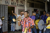 Street band plays and an inhabitant dancing at front of a restaurant in the Central Market of Paramaribo. This is a tradition in Suriname and the bands plays at different locations, places before  important days, festive start.....End of year 2010 celebrations on the streets of Paramaribo. Suriname is one of biggest consumer in South America that using firecrackers, fireworks ( also locally known as pagara ) for celebrations, especially for end of every years and also beginning of every new Chinese Years.