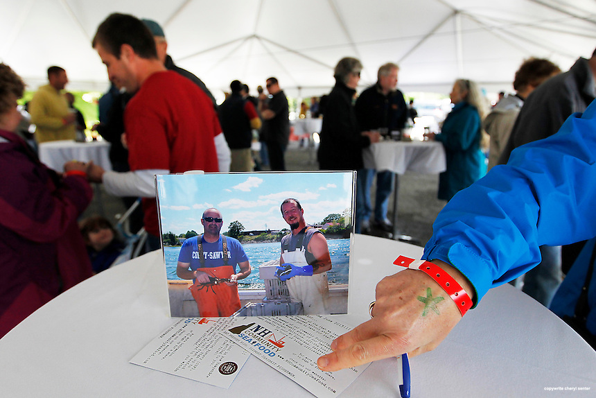 Pictures of local fishermen decorate the tables at The Fresh and Local Seafood 2013 event celebrating the beginning of the commercial fishing season in Portsmouth, N.H., Sunday, May 26, 2013.  (Portsmouth Herald Photo Cheryl Senter)