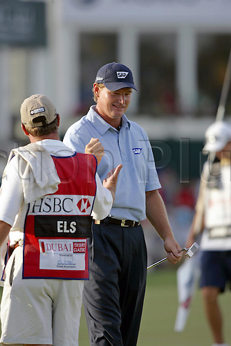 6 March 2005: South African golfer Ernie Els (RSA) high-five's his caddie after making an eagle on the 18th green to win the Dubai Desert Classic held on the Majlis Course at the Emirates Golf Club, Dubai, United Arab Emirates. Els won by one stroke after finishing on 19 under par. Photo: Neil Tingle/Action Plus..050306 male man men golf golfer golfers celebrations celebration celebrates celebrate joy celebrating