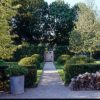 A gravel path leads to a gate in the hedge surrounding the garden