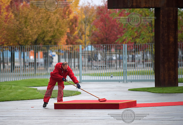 A man cleans the red carpet at the Chancellor's Office during preparations for a state visit.