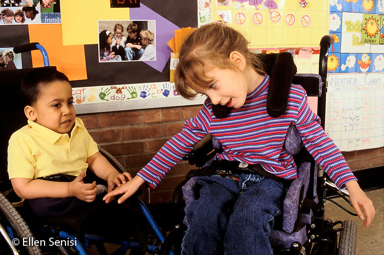 MR / Schenectady, NY.Zoller Public School / Grade 1 Inclusion Class.Girl reaches hand to touch boy as friends talk / Girl: 6, cerebral palsy; Boy: 7, spina bifida, sacral agenesis, Bangledeshi & Puerto-Rican-American..MR: Rah1, Her4.PN#: 30094                     FC#: 21654-00108.scan from slide.© Ellen B. Senisi