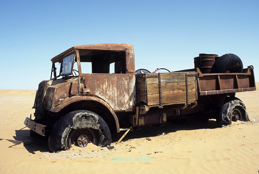 The remnants of a diamond mining truck in the sand and sand dunes in the Namib Naukluft desert.  Access is restricted due to Diamond mining activity by DeBeers.