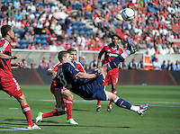 New York forward Kenny Cooper (33) performs a bicycle kick in front of Chicago midfielder Logan Pause (12).  The Chicago Fire defeated the New York Red Bulls 3-1 at Toyota Park in Bridgeview, IL on June 17, 2012.