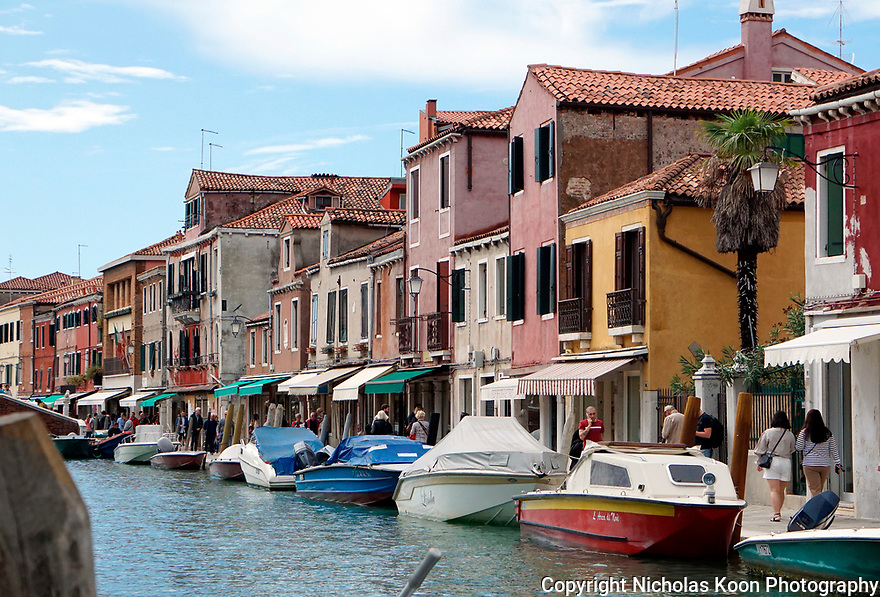 Boats line the shore of the waterfront in Venice surrounded by beautiful historic architecture.