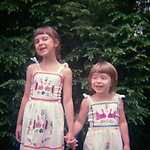 Two young sisters in Mexican sundresses holding hands and smiling in front of Hemlock
