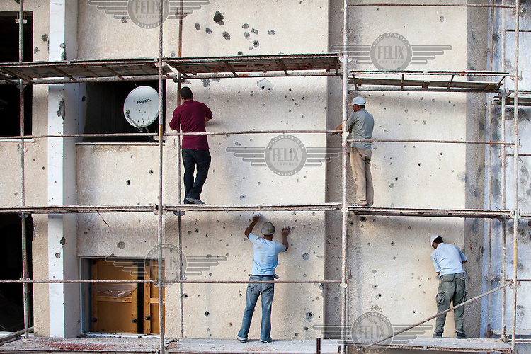 Labourers work to repair bullet holes marking the exterior of the Ailaboun Tower, an 11 storey residential block that was damaged during Operation Cast Lead, an Israeli military operation carried out in 2009.