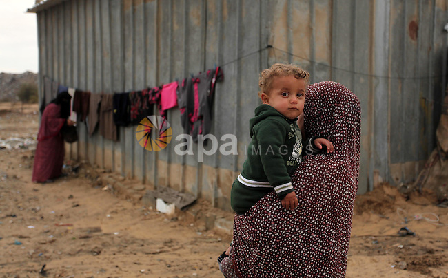 A Palestinian woman carries her son outside her dwelling in Khan Younis in the southern Gaza Strip December 19, 2016. Photo by Ashraf Amra