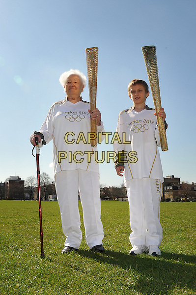 Dinah Gould age nearly 100,  Dominic John MacGowan age 11..Boris Johnson & Jonathan Edwards, introduce the first five torchbearers of the London 2012 Olympic flame, including the oldest and the youngest.  Redlands Primary School, London, England..  .March 19th, 2012.full length white torch looking up tracksuit gold  .CAP/BF.©Bob Fidgeon/Capital Pictures.
