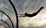 A man flies through the air while working out on the original Muscle Beach rings at Santa Monica State Beach.