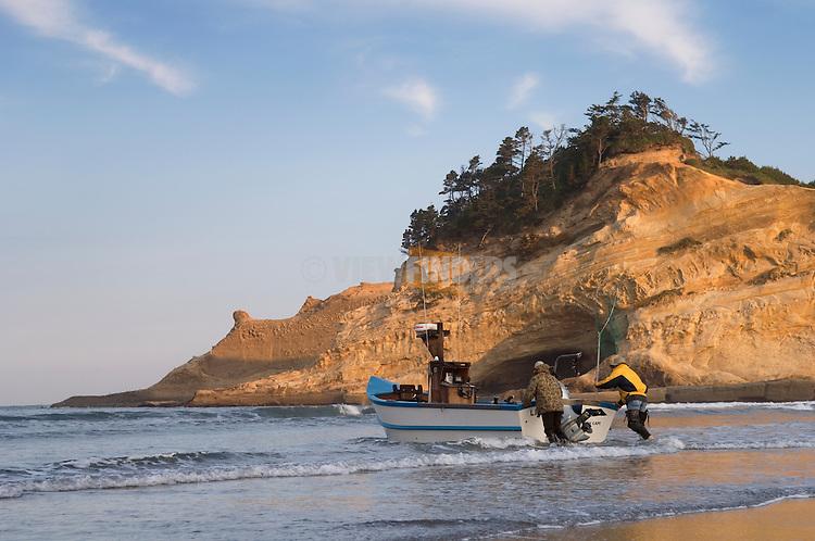 Dory fishermen putting to sea at Haystack Rock and Cape Kiwanda; Pacific City, Oregon Coast..#06061771