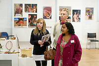 """A current student showing a father & daughter around the exhibition, """"Heart of Brazil"""" by Sue Cunninham.  Open Day at Kingston College when prospective students visit."""