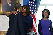 United States President Barack Obama (L) gets a kiss from first lady Michelle Obama after taking the oath of office from U.S. Supreme Court Chief Justice John Roberts and daughter Malia looks on in the Blue Room of the White House in Washington, January 20, 2013. .Credit: Larry Downing / Pool via CNP