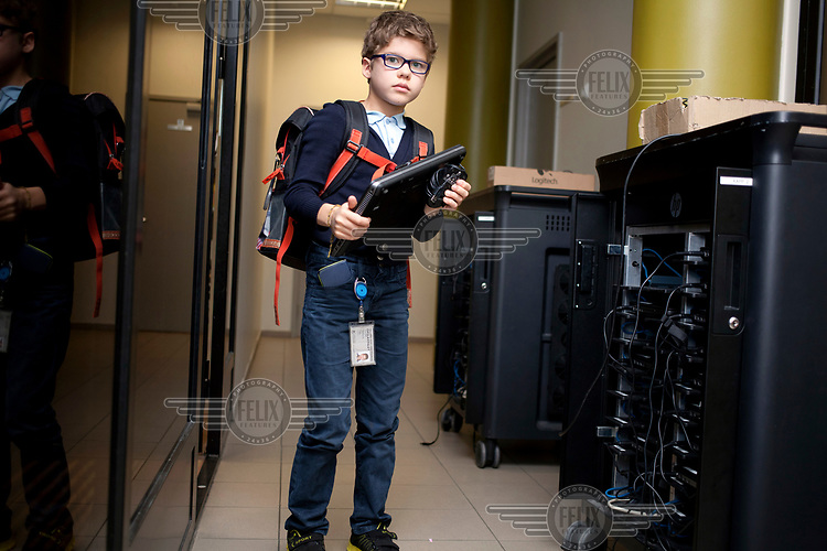 A pupil collects a laptop for a computer science class at the Tallinn Downtown Private School.