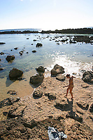 A girl walks on tbe beach at Shark's Cove (or Pupukea beach park) on a calm sunny day.