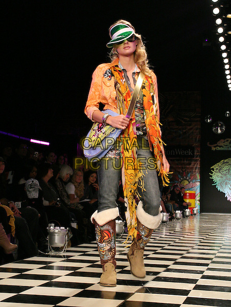 "ED HARDY MODEL.Christian Audigier Presents ""Ed Hardy"" Fashion Show during LA Fashion Week held at Smashbox Studios, Culver City, California, USA..October 13th, 2008.full length catwalk sunglasses shades orange jacket scarf boots jeans denim bag purse blue.CAP/ADM/KB.©Kevan Brooks/AdMedia/Capital Pictures."