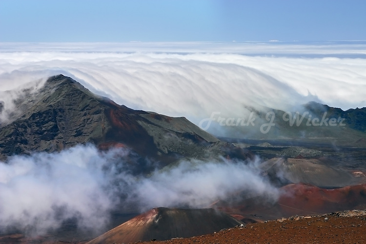 Clouds entering the crater of HALEAKALA NATIONAL PARK on Maui in Hawai appear as a tidal wavei