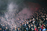 Home supporters shrouded in smoke from a smoke bomb at the start of the second-half at Key's Park during the Hednesford Town (in white) versus FC United of Manchester Northern Premier League premier division play-off final. The match would decide which club were promoted to the Blue Square Conference North. Hednesford won the game by 2 goals to 1 in front of a stadium record attendance of 4412 spectators.