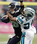 Seattle Seahawks  tight end Jimmy Graham fends off a tackle by Carolina Panthers cornerback Josh Norman (24)  at CenturyLink Field in Seattle on October 18, 2015. The Panthers came from behind with 32 seconds remaining in the 4th Quarter to beat the Seahawks 27-23.  ©2015 Jim Bryant Photography. All Rights Reserved.