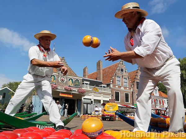 Nederland Edam 2015 07 22 .  Kaasmarkt in Edam . Kaasdragers gooien 2 kaasjes naar elkaar