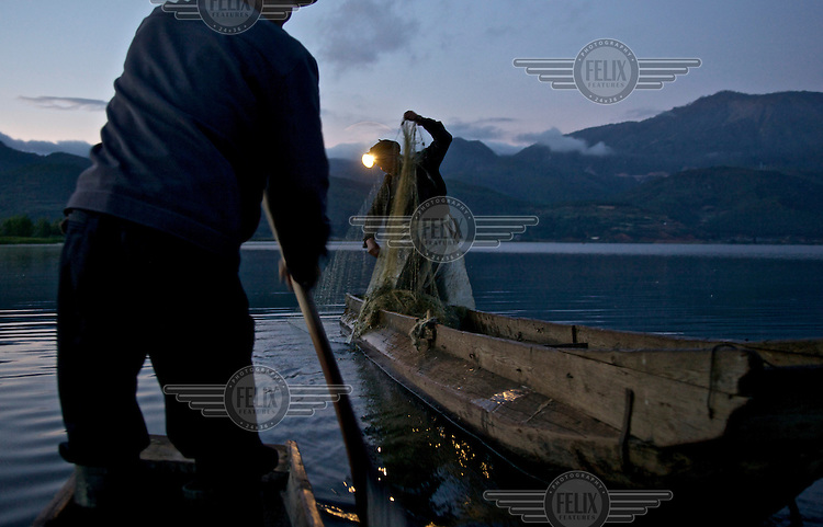 Fishermen haul in their nets at dusk on Lugu Hu Lake. /Felix Features