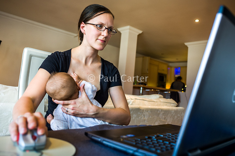 A mother doing home working at her computer while breastfeeding her baby.<br /> <br /> 15/05/2012<br /> Hampshire, England, UK