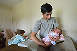 Ahmadullah Ahmadzai holds his one-week old infant daughter Afsana in their home in Harrisonburg, Virginia. Ahmadzai and his family, refugees from Afghanistan, were resettled in Harrisonburg by Church World Service.<br /> <br /> Photo by Paul Jeffrey for Church World Service.