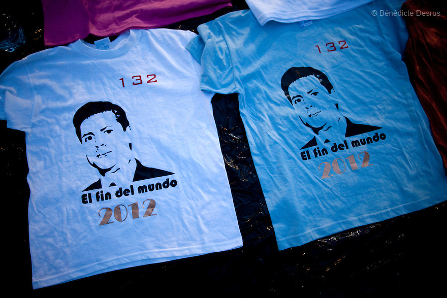 "30 June 2012 - Mexico City, Mexico - Vendors sells tshirt with Message ""132 Pena Nieto, the end of the World 2012"". Thousands of demonstrators and university students members of the movement ?yo soy 132? (I am 132) hold candles during a demonstration to demand transparency in the next election at Zocalo square in Mexico City. ""YoSoy132"" movement was organized by students against the candidature of Enrique Pena Nieto, presidential candidate of the opposition Institutional Revolutionary Party (PRI), who also demanded a balance in the media coverage of the presidential race. Mexico's presidential elections will take place on July 1. Photo credit: Benedicte Desrus"