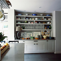 A collection of ceramic pieces and tableware is displayed in a built-in dresser in the sunny kitchen/dining room