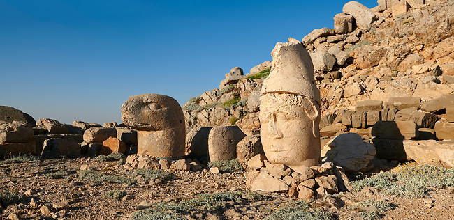 Statue heads, from right, Antiochus, & Eagle, with headless seated statues in front of the stone pyramid 62 BC Royal Tomb of King Antiochus I Theos of Commagene, east Terrace, Mount Nemrut or Nemrud Dagi summit, near Adıyaman, Turkey