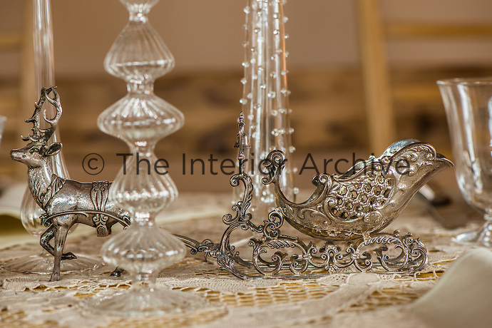 Close-up of a silver ornamental stag and sleigh and glassware on the dining table