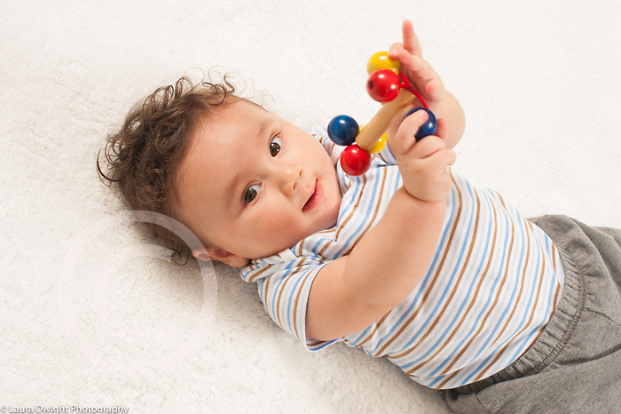 4 month old baby boy on back holding toy and smiling toward viewer