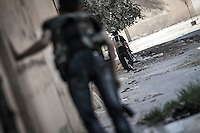 Opposition fighters seep in between buildings and streets as they hide from the Syrian aircraft and helicopter shelling at the industrial Holok neighborhood in north of Aleppo City.