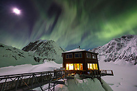 A full moon in the sky with the Aurora Borealis (Northern Lights) above the Sheldon Chalet in the Alaska Range in the Don Sheldon Amphitheater.  Ruth Glacier