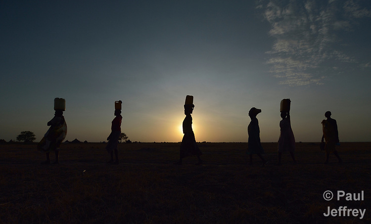 Women carry water to their homes at sunrise on April 12, 2017, in Dong Boma, a Dinka village in South Sudan's Jonglei State. Most of the villagers recently returned home after being displaced by rebel soldiers in December, 2013.<br /> <br /> The women obtained water from a well drilled by the Lutheran World Federation, a member of the ACT Alliance, which is helping villagers restart their lives with support for housing, livelihood, and food security.