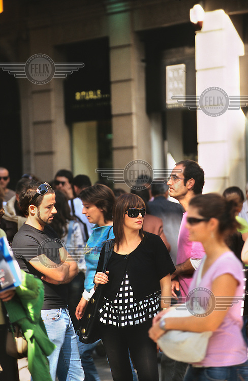Fashionable people walking along the Ramblas in the city centre. .