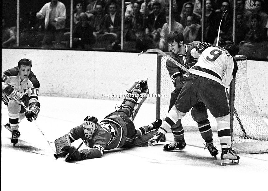 Seals vs Montreal: Ted Hampson and Bill Hicke try to score against goalie Phil Myre, and Guy Lapoint..(1970 photo/Ron Riesterer)