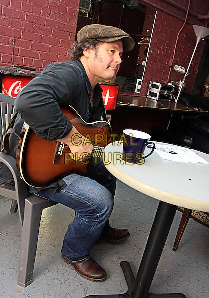Martin Sexton.at Variety Playhouse in Atlanta, Georgia, USA, 6th April 2012.half length black jacket brown flat cap hat sitting table guitar side profile .CAP/ADM/DH.©Dan Harr/AdMedia/Capital Pictures.