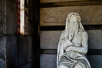 A statue of a pensive man resides inside of a mausoleum in Metairie Cemetery, in New Orleans, Louisiana. In the New Orleans area the water table is too high to bury the dead in the ground. Mausoleums like these are very common.